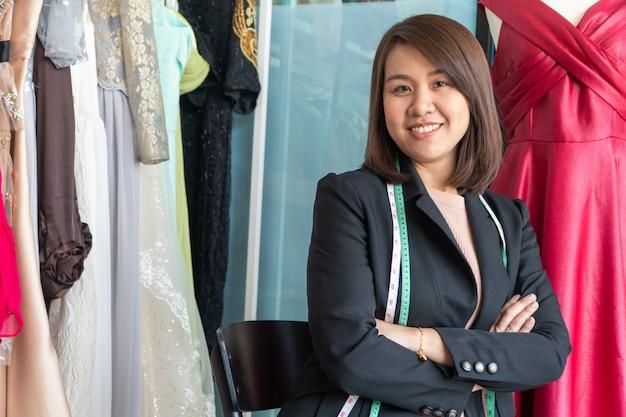 Glückliche junge asiatische schneiderin modedesignerin sucht nach fertigstellung für einen anzug und ein kleid in einem ausstellungsraum.