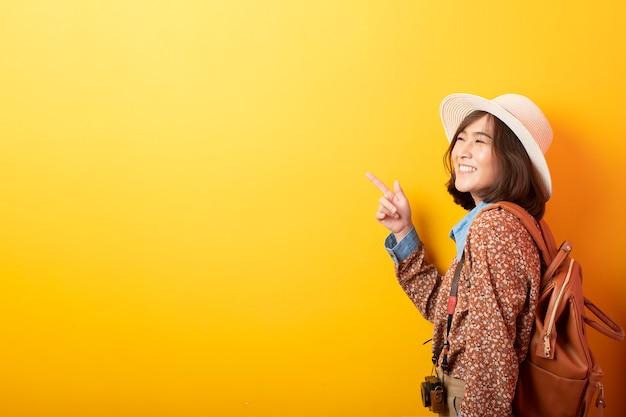 Glückliche junge asiatische touristenfrau auf gelber wand