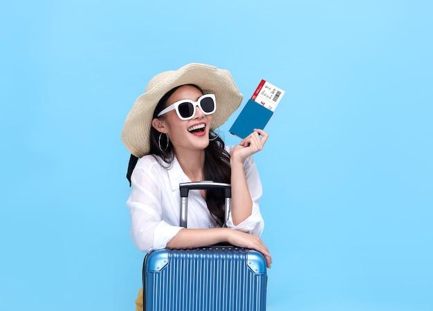Glückliche junge asiatische touristenfrau, die pass und bordkarte mit gepäck hält, das an feiertagen auf blauem hintergrund reisen wird.