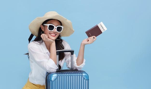 Glückliche junge asiatische touristenfrau zeigt am flughafen einen gesundheitspass der impfbescheinigung, der gegen coronavirus covid-19 geimpft wurde.