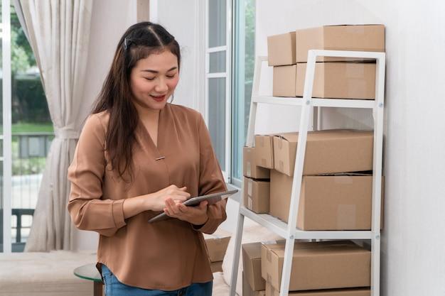 Glückliche junge asiatische unternehmer, die tabletten für scheckbestellung verwenden
