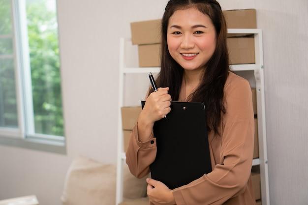 Glückliche junge asiatische unternehmer, die vor regal stehen.