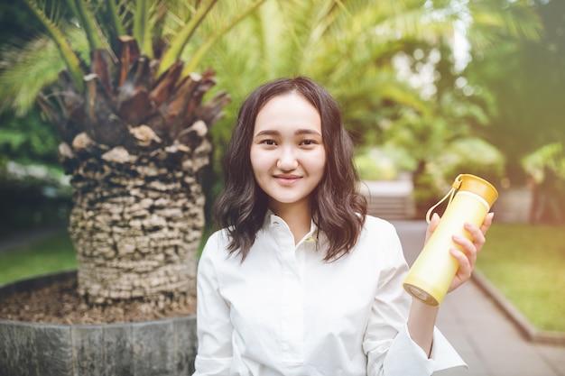 Glückliche junge asiatische weibliche frau in einem park mit wiederverwendbarer plastikflasche