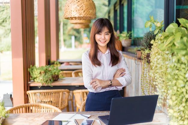 Glückliche junge attraktive asiatische geschäftsfrau, die an der kamera, patio am im freien ihres büros, glücklicher moderner lebensstil steht lächelt