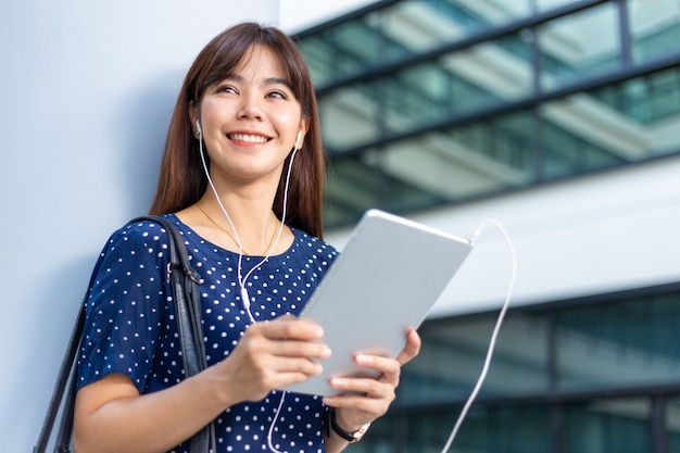 Glückliche junge attraktive asiatische geschäftsfrau in der zufälligen kleidung lächelnd, stehend, an einem gebäude lehnend, halten und hören einen podcast oder eine musik von ihrem tablet-computer