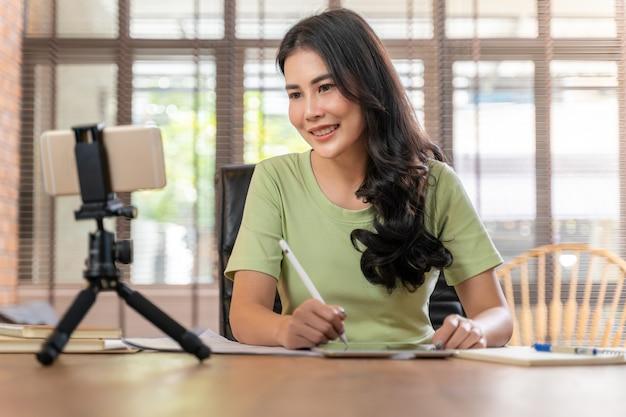 Glückliche junge attraktive frau, die online durch ihr telefon zu hause in ihrem wohnzimmer arbeitet oder lernt