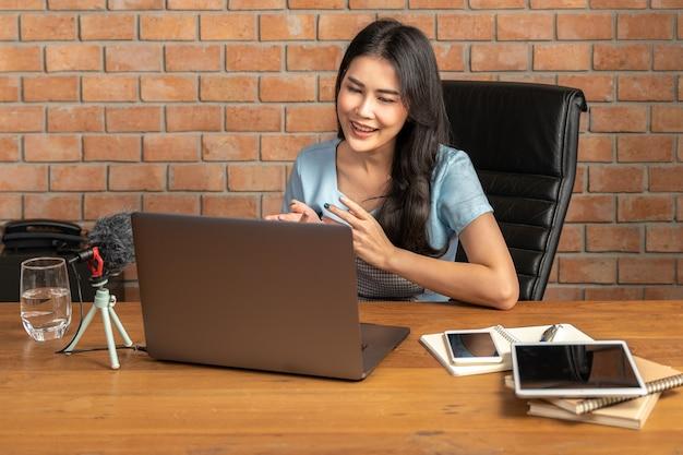 Glückliche junge attraktive frau, die online durch ihren laptop zu hause in ihrem wohnzimmer arbeitet