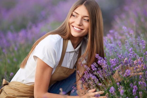 Glückliche junge bäuerin posiert im lavendelfeld