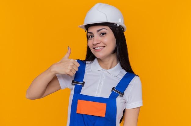 Glückliche junge baumeisterfrau in der bauuniform und im sicherheitshelm, die vorne lächelnd fröhlich zeigt daumen hoch stehend über orange wand