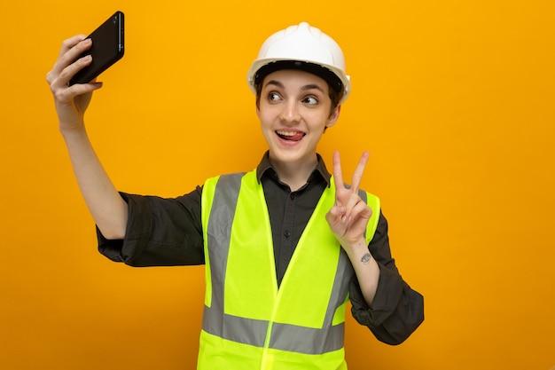 Glückliche junge baumeisterin in bauweste und schutzhelm, die fröhlich lächelt und selfie mit dem smartphone macht, das ein v-zeichen auf orange zeigt