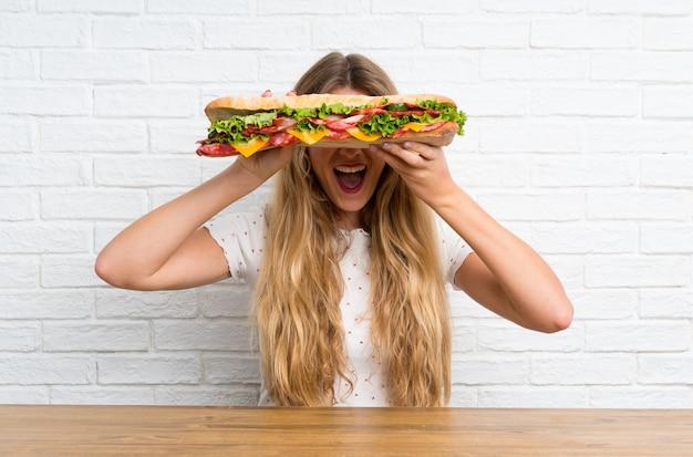 Glückliche junge blonde frau, die ein großes sandwich anhält