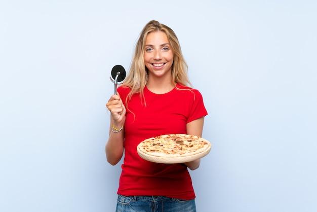 Glückliche junge blonde frau, die eine pizza über getrennter blauer wand anhält