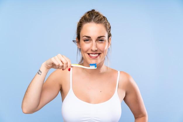 Glückliche junge blonde frau, die ihre zähne putzt