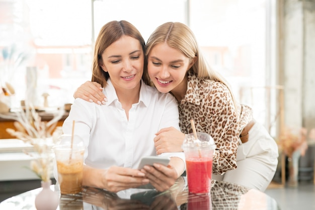 Glückliche junge blonde frau, die ihren freund mit smartphone umarmt, während beide durch waren im online-shop im café scrollen