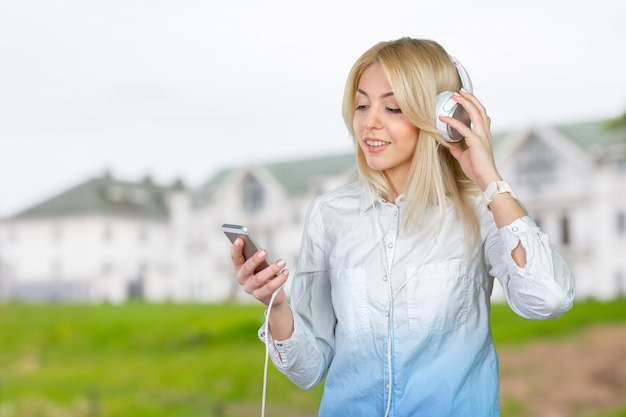 Glückliche junge blonde frau, die musik hört