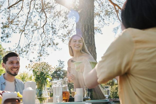 Glückliche junge blonde frau, die plastikbehälter mit salat über serviertem tisch beim abendessen mit ihren freunden unter kiefer nimmt