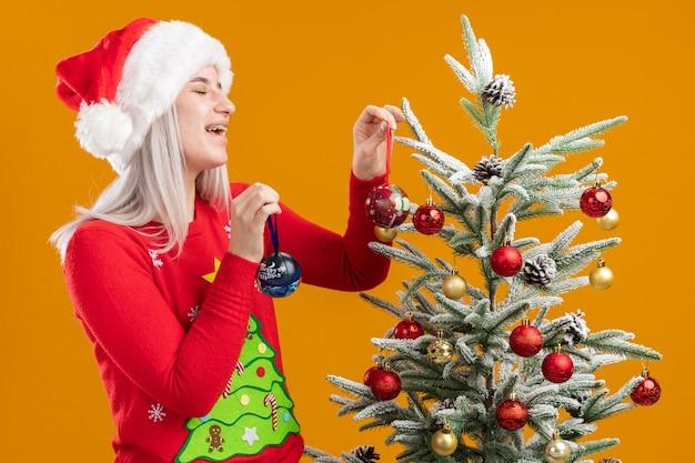 Glückliche junge blonde frau im weihnachtspullover und in der weihnachtsmannmütze, die weihnachtskugeln hält, die neben einem weihnachtsbaum stehen, der baum über orange hintergrund verziert