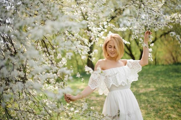Glückliche junge blonde frau im weißen kleid gehend unter weißen blühenden kirschbäumen