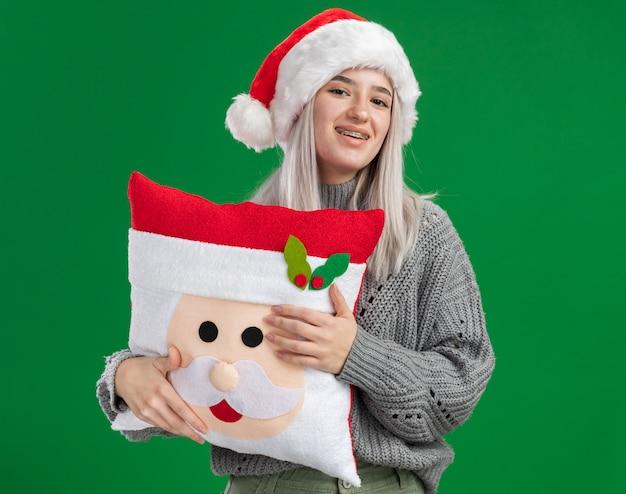 Glückliche junge blonde frau im winterpullover und in der weihnachtsmannmütze, die weihnachtskissen betrachten kamera mit lächeln auf gesicht steht über grünem hintergrund