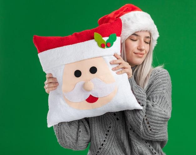 Glückliche junge blonde frau im winterpullover und in der weihnachtsmannmütze, die weihnachtskissen mit den geschlossenen augen halten, die über grünem hintergrund lächelnd stehen