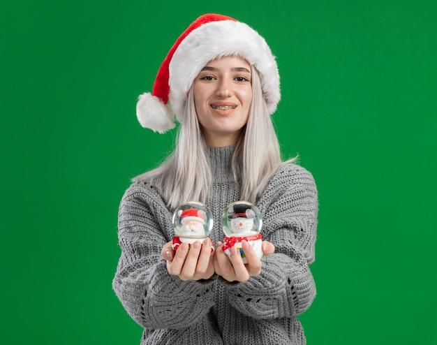 Glückliche junge blonde frau im winterpullover und in der weihnachtsmannmütze, die weihnachtsspielzeug-schneekugeln betrachten, die kamera betrachten, die fröhlich über grünem hintergrund steht