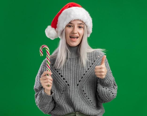Glückliche junge blonde frau im winterpullover und in der weihnachtsmannmütze, die zuckerstange betrachten kamera betrachten, die fröhlich über grünem hintergrund steht
