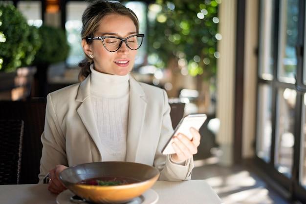 Glückliche junge blonde frau in den gläsern, die in einem restaurant arbeiten