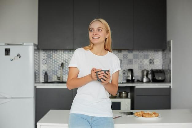 Glückliche junge blonde frau in guter laune steht lehnt sich auf den tisch, lächelt, frühstückt