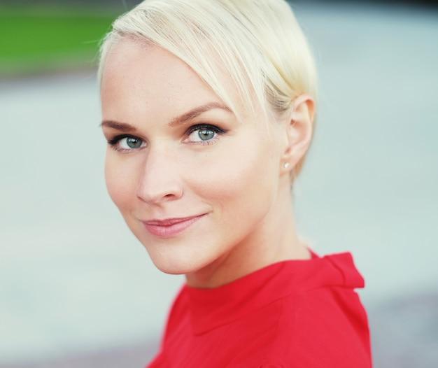 Glückliche junge blonde frau, rotes kleid tragend