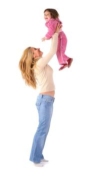 Glückliche junge blonde mutter, die ihre kleine tochter in der rosa kleidung hält und schwingt
