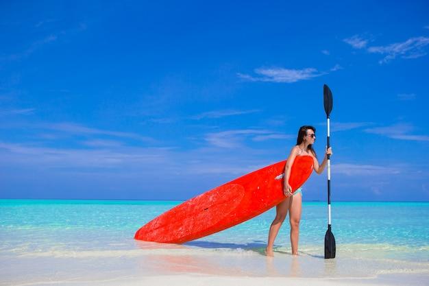 Glückliche junge brandungsfrau am strand mit einem surfbrett und einem paddel