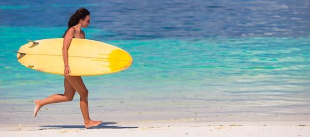 Glückliche junge brandungsfrau, die am strand mit einem surfbrett läuft
