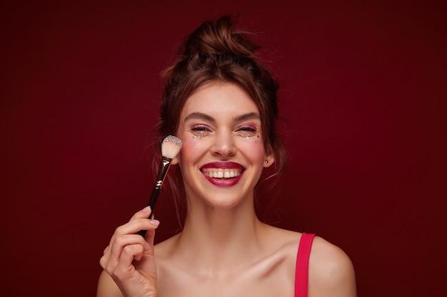 Glückliche junge braunhaarige reizende frau mit festlichem make-up, das lässige frisur im stehen trägt, sich mit freunden am abend trifft und in hochstimmung ist