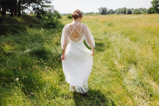 Glückliche junge braut in einem weißen hochzeitskleid des kiefernwaldes