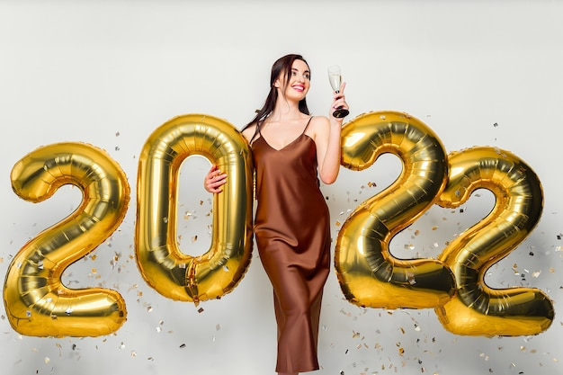 Glückliche junge brünette frau mit glas champagner in der nähe von goldenen luftballons auf weißem hintergrund...