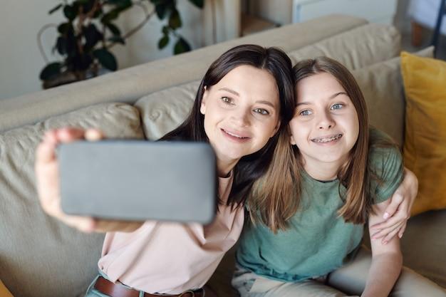 Glückliche junge brünette frau mit smartphone und ihrer lächelnden tochter im teenageralter, die beim sitzen auf der couch selfie macht