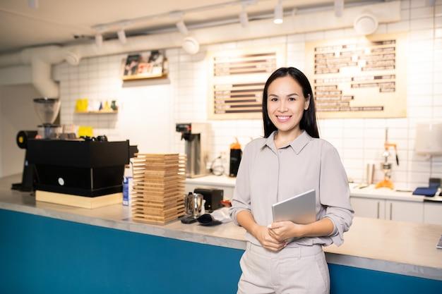 Glückliche junge brünette kellnerin, die digitales tablett hält, während sie durch zähler steht und auf sie im café oder im restaurant wartet