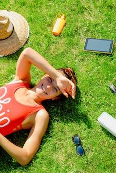 Glückliche junge brunettefrau, die musik im freien an einem sommertag hört