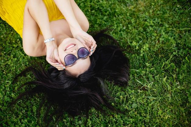 Glückliche junge brunettefrau in der sonnenbrille, die auf dem gras, draufsicht liegt