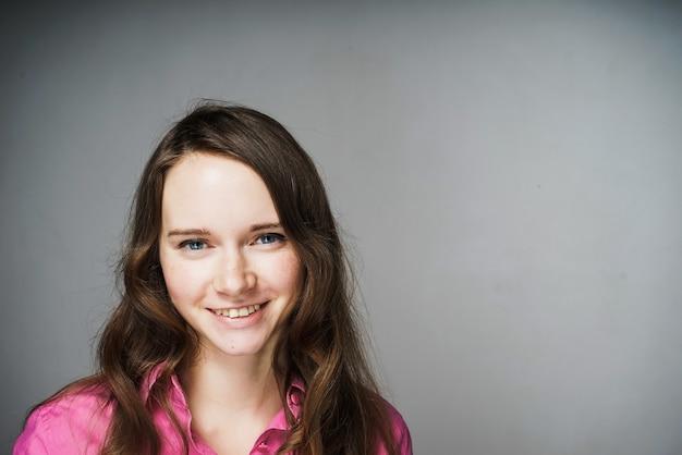 Glückliche junge büroangestellte in einem rosa hemd lächelnd