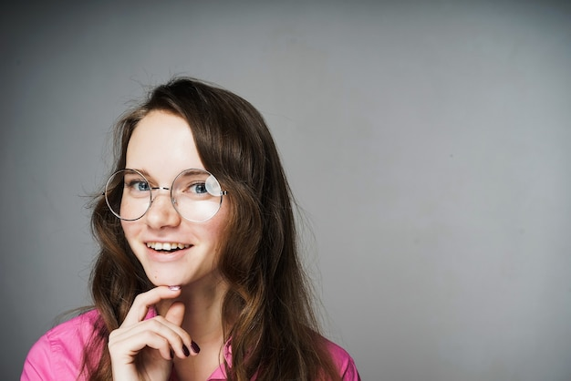 Glückliche junge büroangestellte in einem rosa hemd und einer brille lächelnd