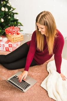 Glückliche junge dame, die laptop nahe geschenkboxen und weihnachtsbaum verwendet