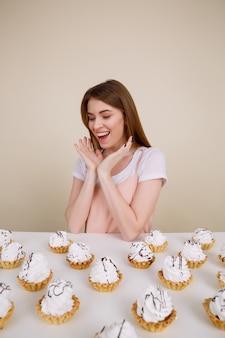 Glückliche junge dame, die nahe cupcakes sitzt und aufwirft