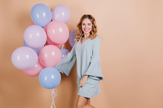 Glückliche junge dame im trendigen blauen kleid, das mit partyballons aufwirft
