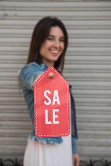 Glückliche junge dame mit verkaufstablette nahe profilierter bedeckungswand