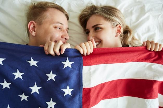 Glückliche junge datteln, die mit amerikanischer flagge bedecken, während sie auf bett liegen