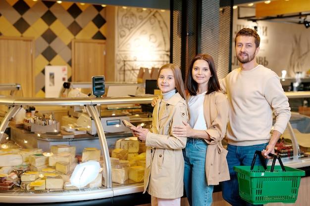 Glückliche junge dreiköpfige familie, die mit milchprodukten beim besuch des modernen supermarlets zur verfügung steht