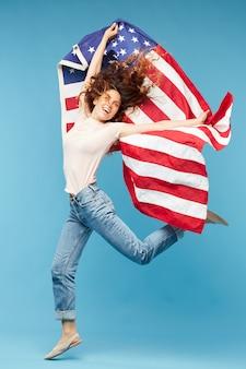 Glückliche junge dynamische frau, die isoliert mit amerikanischer nationalflagge tanzt