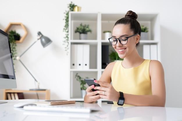 Glückliche junge elegante geschäftsfrau mit dem zahnigen lächeln, das in smartphone rollt, während pause durch arbeitsplatz genießen