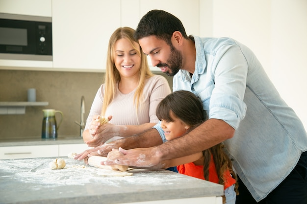Glückliche junge eltern, die tochter lehren, teig auf küchenschreibtisch mit mehl unordentlich zu rollen. junges paar und ihr mädchen backen brötchen oder kuchen zusammen. familienkochkonzept